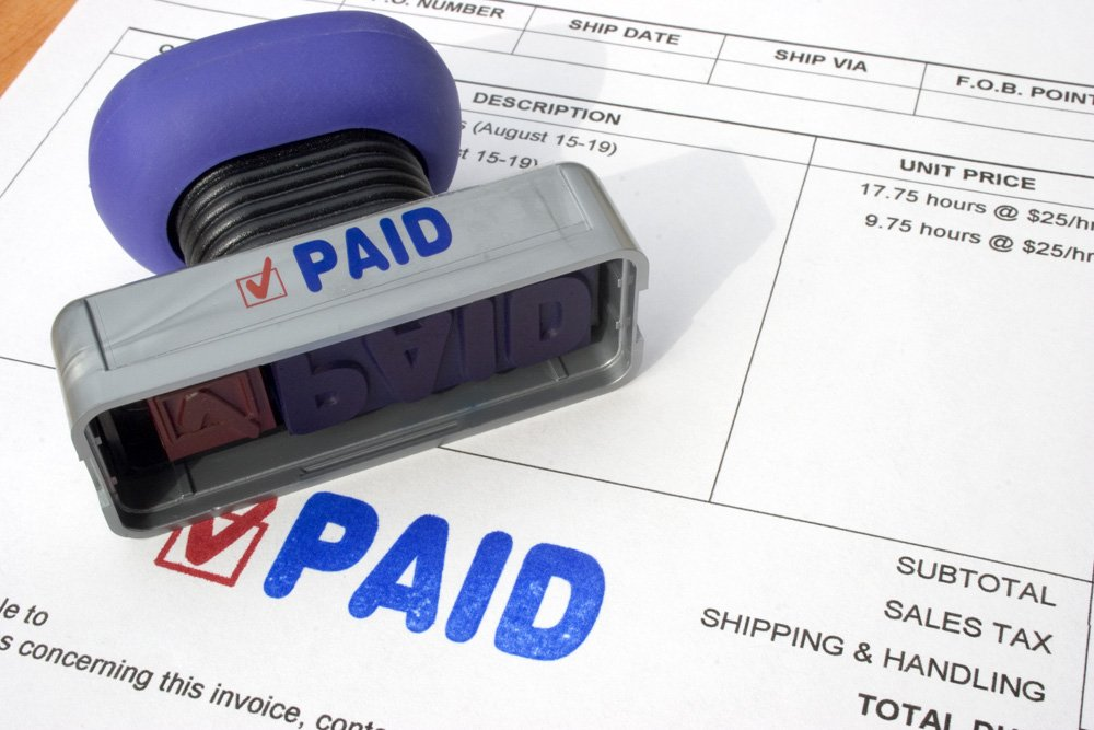 Accounts payable invoice with paid stamped on the page.