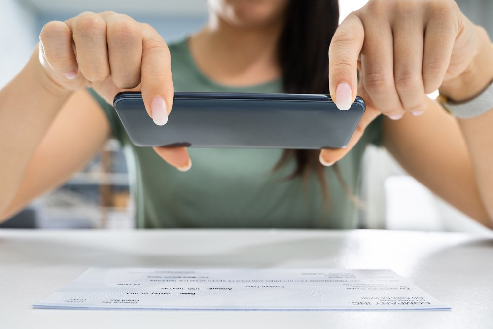 Woman taking photo of check for accounts receivables process.